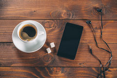 Mobile phone with headphones, a Cup of coffee Stock Photography
