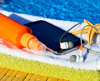 Mobile phone, headphones, starfish and towels. Royalty Free Stock Photos