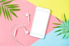 Mobile phone headphones summer holidays flat lay background Stock Photos