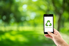 mobile phone holding hand with recycle symbol eco environment Royalty Free Stock Image