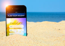 Mobile phone with holiday planner on the beach. Sea as a background Stock Images