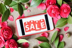 Mobile phone with inscription sale and pink roses. Flat lay, top view royalty free stock photos