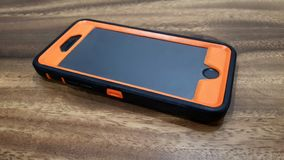 Iphone 6 mobile phone in faux otterbox casing. Mobile phone iphone 6 on table with thick orange casing royalty free stock photography