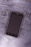 Mobile phone on the jeans background Royalty Free Stock Photos