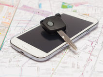 Mobile phone and key car on the map. Royalty Free Stock Images