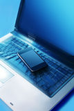 Mobile phone on the keyboard Stock Images