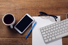 Mobile phone, keyboard, paper, spectacles, pen and coffee on wooden table. Close-up of mobile phone, keyboard, paper, spectacles, pen and coffee on wooden table Stock Photos