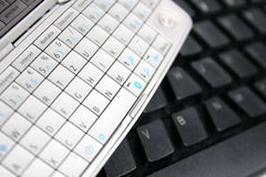Mobile phone keypad and computer keyboard. In closeup Royalty Free Stock Images