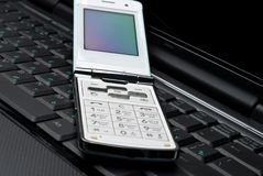 Mobile phone on a laptop. Cellular phone on a laptop Stock Photo