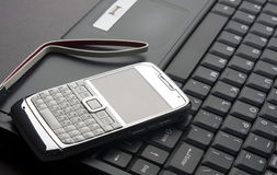 Mobile phone on a laptop Royalty Free Stock Photo