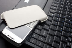 Mobile phone on a laptop Stock Photo