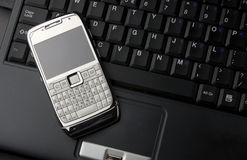 Mobile phone on a laptop Royalty Free Stock Photos