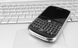 Mobile phone on a laptop. Black mobile on silver computer Royalty Free Stock Image