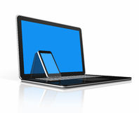 Mobile phone on a laptop Stock Images
