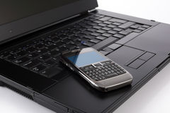 Mobile phone on laptop computer royalty free stock photo