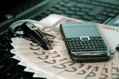 Mobile phone, laptop keyboard, bluetooth and cash. Mobile phone, laptop keyboard, bluetooth handsfree headset and money Royalty Free Stock Photos