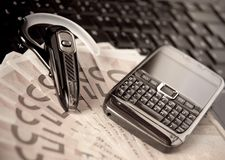 Mobile phone, laptop keyboard, bluetooth and cash. Mobile phone, laptop keyboard, bluetooth handsfree headset and money Stock Photo