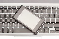Mobile phone with laptop keyboard Stock Photo