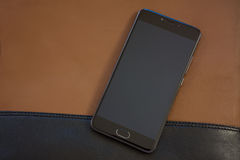 Mobile phone on leather bag. Mobile phone on the brown leather bag royalty free stock photos