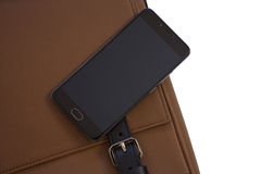 Mobile phone on leather bag. Mobile phone on the brown leather bag stock photo