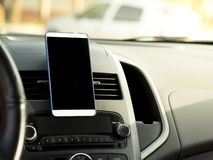 Mobile phone located in the center of the vehicle console. Black screen phone in the car stock photography