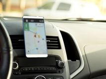 Mobile phone located in the center of the vehicle console. Blank screen phone in the car stock photography