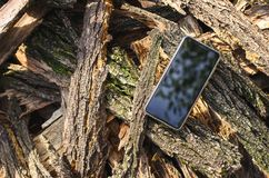 Mobile phone black color is located in the open air on a pile of bark from acacia trees Royalty Free Stock Photos