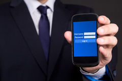 Mobile phone with login screen in business man hand Stock Photography