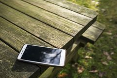 Mobile phone is lying dangerously on the edge of a wooden table carelessly left with the possibility of falling, outdoors, in the. Rays of the spring sun stock photos