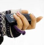 Mobile phone in the maiden hand. The girl holds phone in a hand. The winter, on a hand is dressed a glove. The photo is made in November 2009 royalty free stock photos