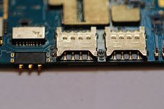 Mobile phone main board. With two SIM slots and memory card holder. Close-up with selective Royalty Free Stock Photo