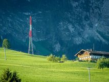 Mobile phone mast with farm house. Red and white mobile phone pylon near a farm house in austria royalty free stock image