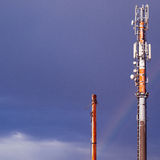Mobile phone mast. With rainbow behind royalty free stock photography