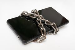 Mobile phone with metal chain locked on white Royalty Free Stock Images
