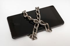 Mobile phone with metal chain locked on white Stock Images