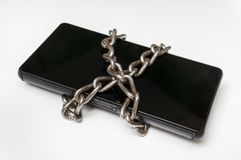 Mobile phone with metal chain locked on white Royalty Free Stock Photos