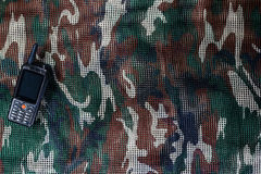 Mobile phone on military camouflage net background Royalty Free Stock Photos