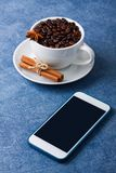Mobile phone mockup cup of coffee seeds cinnamon anis. Mobile phone mockup on blue table and cup of coffee wit seeds, cinnamon and anis. Vertical orientation Royalty Free Stock Photography