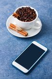 Mobile phone mockup cup of coffee seeds cinnamon anis. Mobile phone mockup on blue table and cup of coffee wit seeds, cinnamon and anis. Vertical orientation Stock Photography