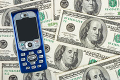 Mobile phone on money background Royalty Free Stock Images