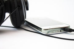 Mobile phone or mp3 player and big headset Stock Photos