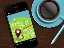 Mobile phone with navigation application, coffee and pencil lyin. G on wooden desk Stock Photo