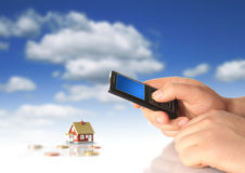 Mobile phone and new house. Royalty Free Stock Photo