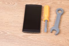 Mobile phone next to plastic tools. On wooden service, repair concept royalty free stock photo