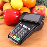 Mobile phone with NFC technology on payment terminal and fruits with vegetables, cashless paying for shopping. Payment terminal, credit card reader with mobile Stock Images