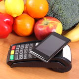 Mobile phone with NFC technology on payment terminal and fruits with vegetables, cashless paying for shopping. Payment terminal, credit card reader with mobile Royalty Free Stock Image