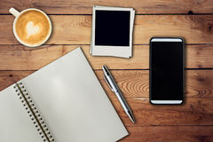 Mobile phone, notebook pen, photo frame and coffee cup on office Royalty Free Stock Photo