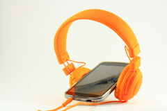 Mobile phone and orange headphones Royalty Free Stock Images
