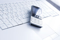 Mobile phone over laptop Stock Image