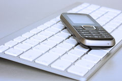 Mobile phone over laptop keyboard stock images